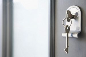 Close up of key in a front door --- Image by © James French/Image Source/Corbis